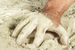 Sirva la mano con los fingeres cubiertos con la arena blanca Imagenes de archivo