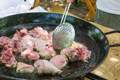 Sirva la mano del ` s con la desnatadora que vuelca la carne del pollo que fríe en chisporrotear el aceite de oliva en cacerola p Foto de archivo libre de regalías