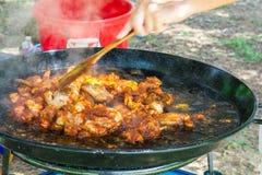 Sirva la mano del ` s con Turner de madera que mezcla la carne del pollo frito con la salsa de tomate en cacerola plana grande Pr Foto de archivo