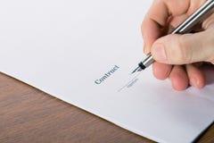 Sirva la mano del ` s con una muestra de la pluma un contrato fotografía de archivo libre de regalías