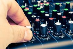 Sirva la mano del ` s que ajusta el primer de mezcla de los botones de la consola Imagen de archivo