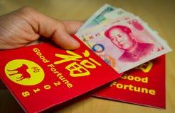 Sirva la mano del ` s que da un sobre o un bao rojo de hong durante Año Nuevo chino en 2018 o persiga el año del ` s Imagen de archivo