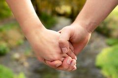 Sirva la mano del ` s que detiene firmemente a la hembra contra la perspectiva de t fotos de archivo