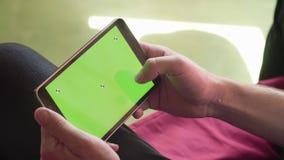 Sirva la mano del ` s que enrolla una tableta con la pantalla verde almacen de metraje de vídeo