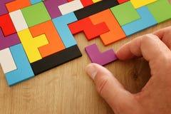Sirva la mano del ` s que lleva a cabo un rompecabezas cuadrado del rompecabezas chino, sobre la tabla de madera imagen de archivo