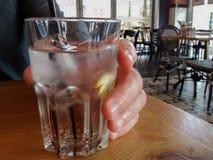 Sirva la mano del ` s que se sostiene de cristal con agua, los cubos de hielo, el limón y la paja imagen de archivo