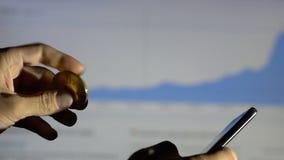 Sirva la mano del ` s que sostiene Bitcoin de oro y guarda el teléfono en fondo financiero almacen de video