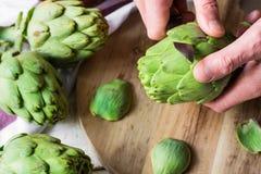 Sirva la mano del ` s que sostiene el cuchillo y que pela las alcachofas frescas, preparándose para cocinar, tabla de cortar Fotografía de archivo libre de regalías