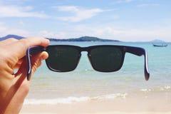 Sirva la mano del ` s que sostiene las gafas de sol del estilo del inconformista en la playa de Rawai Concepto despreocupado del  Imagenes de archivo