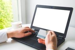 Sirva la mano del ` s que sostiene la tarjeta de crédito y que incorpora datos confidenciales al ordenador portátil para hacer la Foto de archivo