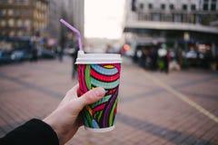 Sirva la mano del ` s que sostiene un color brillante y una taza de café de papel en el fondo de la ciudad Imagen de archivo libre de regalías