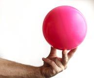 Sirva la mano del ` s que sostiene una bola para la gimnasia Imagenes de archivo