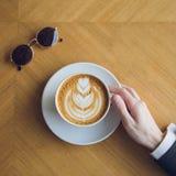 Sirva la mano del ` s que sostiene una taza de café Foto de archivo libre de regalías