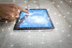 Sirva la mano del ` s usando la tableta con la conexión de la comunicación del mapa del mundo y del web en el escritorio de mader Imagenes de archivo