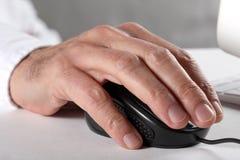 Sirva la mano del ` s usando un ratón del ordenador y un teclado imagen de archivo