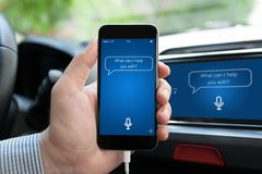 Sirva la mano en el coche que sostiene el teléfono con el ayudante personal del app imagen de archivo libre de regalías