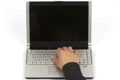 Sirva la mano en el teclado del ordenador portátil con el monitor de la pantalla en blanco imagen de archivo libre de regalías