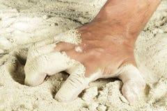 Sirva la mano que coge un puñado de arena Imágenes de archivo libres de regalías