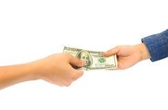Sirva la mano que da el billete de banco americano del dólar a la mano del niño Imagen de archivo libre de regalías