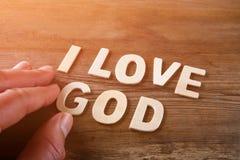 Sirva la mano que deletrea a dios de letras de madera, imagen retra del amor de la palabra i del estilo Foto de archivo