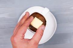 Sirva la mano que lleva a cabo el cuadrado del chocolate blanco sobre la taza Fotos de archivo