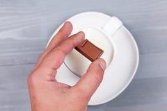 Sirva la mano que lleva a cabo el cuadrado del chocolate sobre la taza de leche Foto de archivo libre de regalías