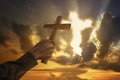 Sirva la mano que lleva a cabo la forma de madera del símbolo de la cruz o de la religión Fotografía de archivo libre de regalías