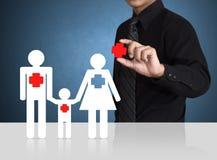 Sirva la mano que lleva a cabo símbolo del seguro con la familia de papel Imagenes de archivo
