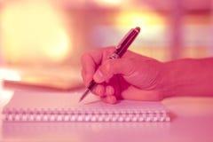 Sirva la mano que lleva a cabo una escritura de la pluma en el cuaderno Foto de archivo libre de regalías