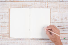 Sirva la mano que sostiene el lápiz y que escribe el cuaderno en la tabla de madera para Imágenes de archivo libres de regalías
