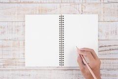 Sirva la mano que sostiene el lápiz y que escribe el cuaderno en la tabla de madera para Fotos de archivo
