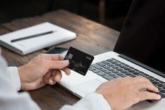 Sirva la mano que sostiene la tarjeta de crédito y que mecanografía el ordenador portátil fotografía de archivo libre de regalías