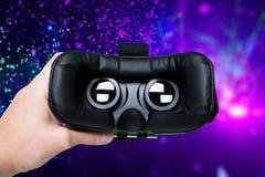 Sirva la mano que sostiene los vidrios de VR en fondo colorido Visión superior/mano Fotografía de archivo