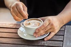Sirva la mano que sostiene la taza de café en la tabla de madera vieja Imágenes de archivo libres de regalías