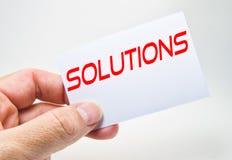 Sirva la mano que sostiene una cartelera gris con la palabra de la solución escrita en ella en un fondo blanco imagen de archivo