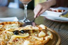Sirva la mano que toma la rebanada de pizza del tablero de madera La gente come los alimentos de preparación rápida en café Imagenes de archivo