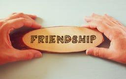 Sirva la mano y la mano de la mujer que llevan a cabo la muestra con la amistad de la palabra Imágenes de archivo libres de regalías