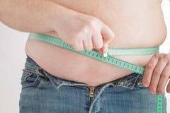 Sirva la medición de su vientre gordo con la cinta de la medida Foto de archivo libre de regalías