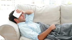 Sirva la mentira en el enfermo del sofá con una temperatura almacen de video