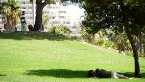 Sirva la mentira en la hierba de un parque al lado de un árbol almacen de metraje de vídeo