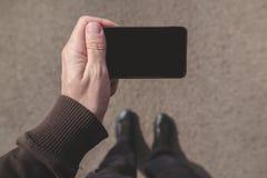 Sirva la mirada de la pantalla del smartphone mientras que camina en la calle Fotografía de archivo