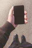 Sirva la mirada de la pantalla del smartphone mientras que camina en la calle Fotografía de archivo libre de regalías