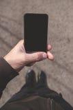 Sirva la mirada de la pantalla del smartphone mientras que camina en la calle Imagen de archivo