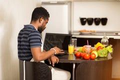 Sirva la mirada de receta en el ordenador port?til en cocina en casa imagenes de archivo