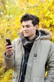 Sirva la mirada en su teléfono móvil en parque del otoño Imagen de archivo