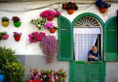 Sirva la mirada hacia fuera de la puerta de su casa con la fachada adornada con las macetas coloridas Foto de archivo