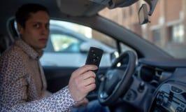 Sirva la mirada hacia fuera de la ventanilla del coche y llevar a cabo una llave de la alarma para coches Fotografía de archivo