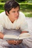 Sirva la mirada a su cara mientras que lee un libro como él miente en un bla Fotografía de archivo libre de regalías