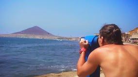 Sirva la mirada a través de los prismáticos en la costa del mar azul almacen de metraje de vídeo