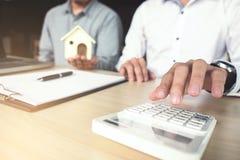 Sirva la muestra una póliza de seguro casera en préstamos hipotecario, agente lleva a cabo préstamo Fotografía de archivo libre de regalías